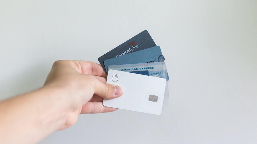 Man holding multiple credit cards used to pay for coaching services known as credit card stacking or loan stacking.