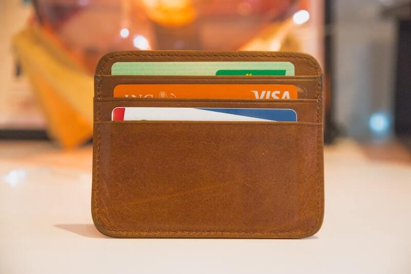 Wallet filled with credit cards used to pay for coaching services, also known as credit card stacking.