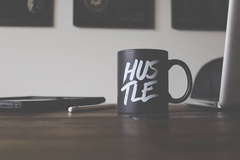 Hustle coffee cup that is used by a coach who offers financing for coaching programs.
