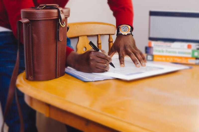 Man signing loan documents he is using for loan stacking to pay for online coaching programs.